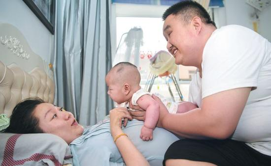 Zhang Yongfei and his wife, Tian Xiao, play with their son at their home. (Photo: Wei Liang / China News Service)