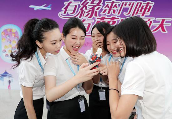 Airline cabin crew members from Taiwan attend an inauguration ceremony held by Xiamen Airlines on Aug 16. The company, based in Xiamen, Fujian Province, has hired 104 flight attendants from the island this year. (CHEN LIJIE/FOR CHINA DAILY)