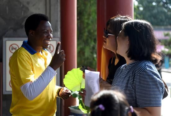 Volunteer Irivuzimana Felicien, a Rwandan graduate student at Beijing Jiaotong University, greets a visitor at Yuanmingyuan Park, or the Old Summer Palace, on Monday. (LI LEI/CHINA DAILY)