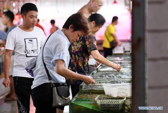 Customers buy seafood in a market in Nanning, South China's Guangxi Zhuang autonomous region, June 9, 2018. (Photo/Xinhua)
