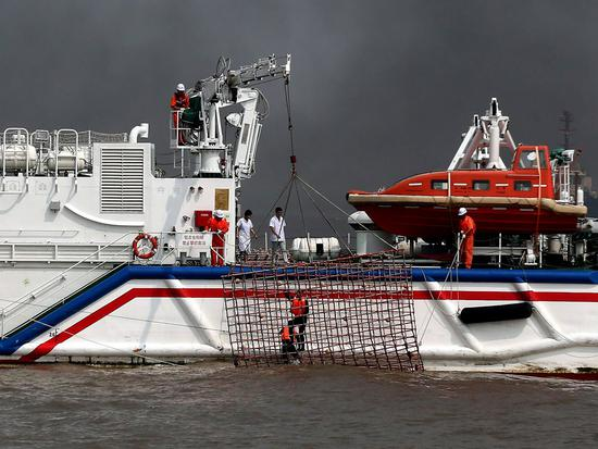 Drowning sailors are saved by a rescue ship during the oil slick emergency response drill. (Photo by Shen Lei/For China Daily)