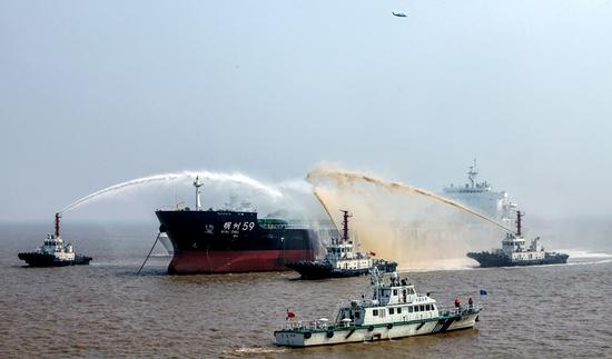 Rescue ships spray an oil tanker with fire-extinguishing chemicals to battle a simulated fire during a drill off Zhoushan, Zhejiang province, on Tuesday. (Photo by Hua Zhibo/for China Daily)