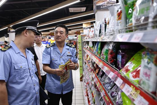 Inspectors check the food quality at a supermarket in Beijing's Xicheng district on Wednesday. (Zou Hong/China Daily)