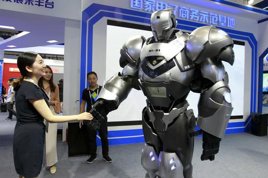 A visitor to a service trade expo interacts with a robot on display at the event. (Photo by A Jing/For China Daily)