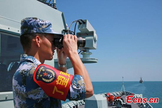 A Chinese soldier watches through a telescope onboard Chinese frigate Huangshan during Exercise KAKADU 2018 at sea off the coast of Darwin, Australia, Sept. 6, 2018. (Photo: China News Service/Xu Guang)