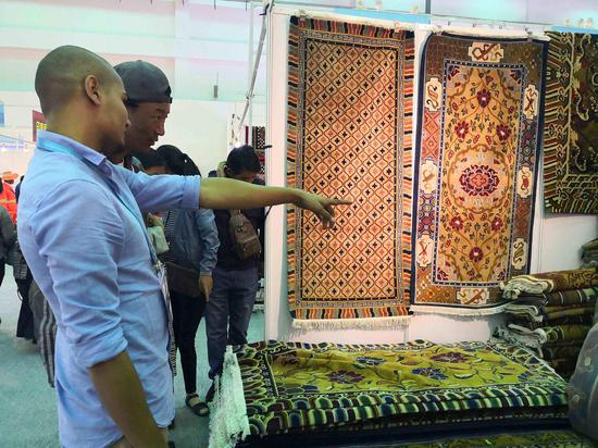 Nepali businessmen promote their carpets at the 4th China Tibet Tourism and Culture Expo on September 8, 2018, in Lhasa, Tibet Autonomous Region.(Photo by CGTN)