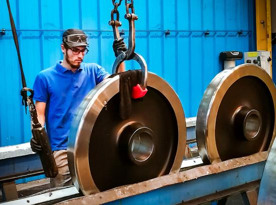 A worker of Valdunes, a French high-speed train wheel manufacturer, repackages the Ma Steel high-speed train wheels to be shipped to Germany. (Photo provided to China Daily)