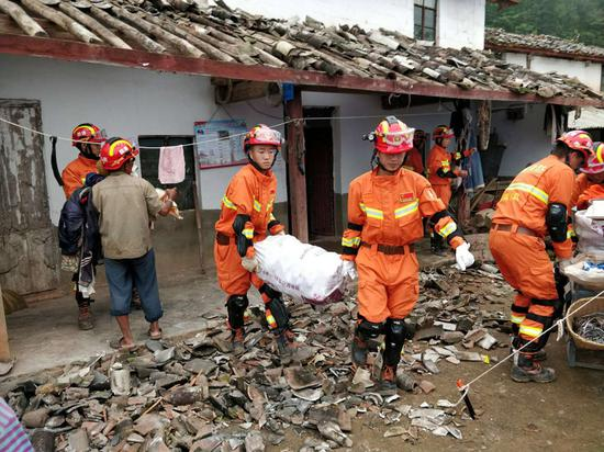 Rescuers help villagers move their belongings in a village in Mojiang Hani autonomous county, Yunnan province, on Sunday. A magnitude 5.9 earthquake hit the region on Saturday morning. (Provided to China Daily)