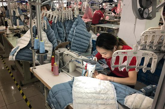 Employees work at Jintongwang Dress Co in Zhili, Zhejiang province. The company produces one of China's top brands of children's clothing. (Photo by Ma Zhenhuan/China Daily)