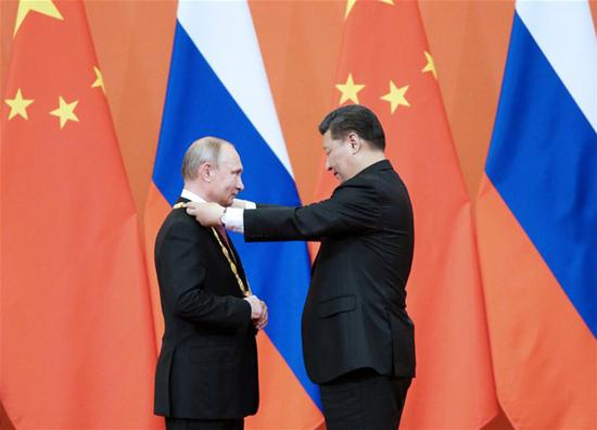 President Xi Jinping awards his Russian counterpart Vladimir Putin the first-ever Friendship Medal of the People's Republic of China at the Great Hall of the People in Beijing, June 8, 2018. (Photo/Xinhua)