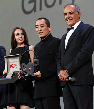Director Zhang Yimou receives and holds the Jaeger-LeCoultre Glory to the Filmmaker prize awarded to him ahead of the world premiere of Shadow during 75th Venice International Film Festival in Venice, Italy, Sept 6, 2018. (Photo provided to China.org.cn by Le Chuang Entertainment)