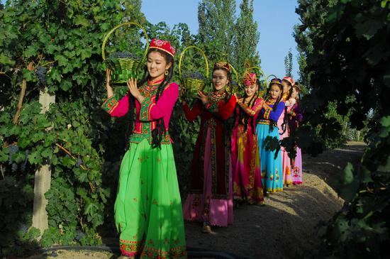 Women dressed in colorful outfits perform at the 27th Silk Road Turpan Grape Festival in Turpan, Northwest China's Xinjiang Uygur autonomous region, Sept. 3, 2018. (Photo provided to Chinadaily.com.cn)
