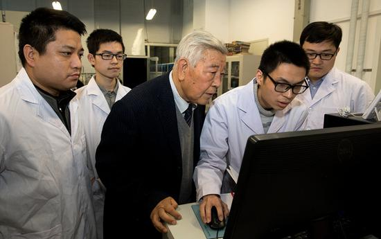Academician Zhao Zhongxian discusses superconductive materials with his students in Beijing. (Photo/Xinhua)