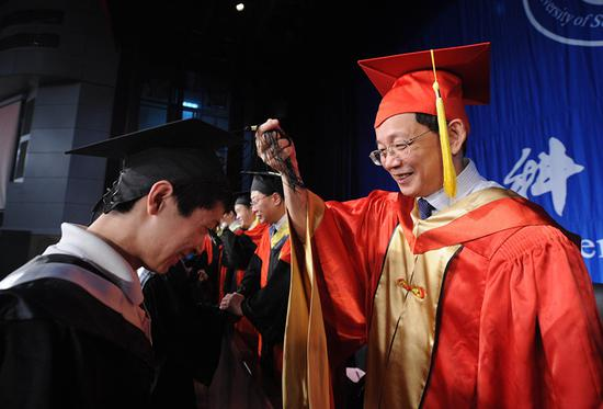 Hou Jianguo, vice president of the Chinese Academy of Sciences, interacts with a graduate at a ceremony in Anhui Province. (Photo/Xinhua)