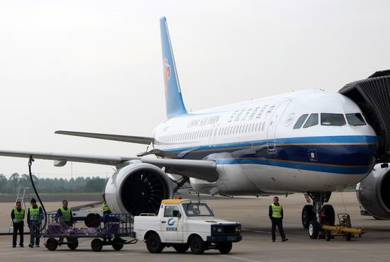Ground staff deliver passengers' luggage onto an airplane of China Southern Airlines in Changzhou, Jiangsu Province. (Photo by Zhen Huai/For China Daily)