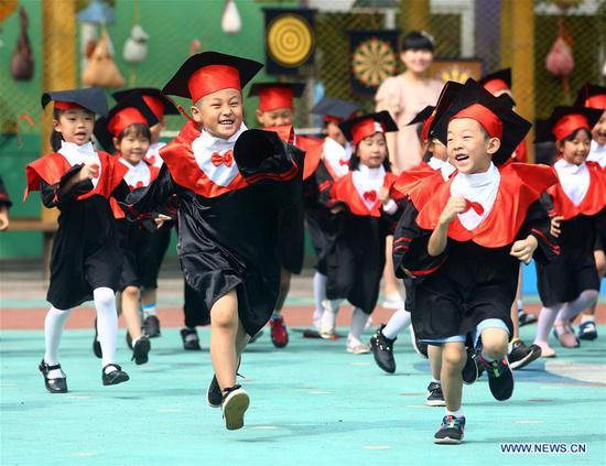 Kindergarten children wearing gowns of Doctor Degree run at the Hedong District No 2 Kindergarten in Tianjin, North China, June 17, 2016. (Photo/Xinhua)