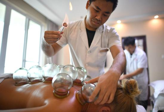 Russian tourists receive traditional Chinese medicine therapy from medical staff at Sanya International Friendly Chinese Medicine Sanatorium in Hainan Province in June. (GUO CHENG / XINHUA)