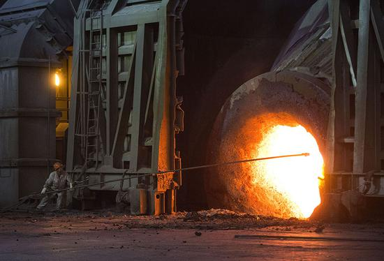 An employee moves molten iron at a furnace in a production area of Baowu Steel Group in Wuhan, capital of Hubei Province. (Photo provided to China Daily)