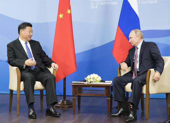 Xi, Putin vow to promote ties