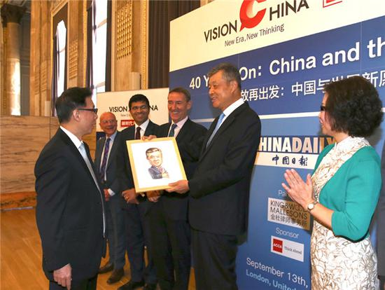 Editor-in-Chief of China Daily Zhou Shuchun (L1) gives gifts to guest speakers at China Daily's Vision China event in London, Sept 13, 2018. (Photo by Zou Hong/chinadaily.com.cn)