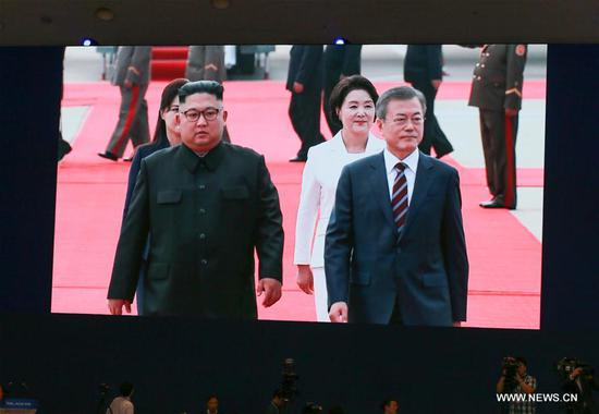 Photo taken on Sept. 18, 2018 at the press center for the 2018 Inter-Korean Summit in Seoul, South Korea, shows a live broadcast showing Top leader of the Democratic People's Republic of Korea (DPRK) Kim Jong Un (L) welcoming South Korean President Moon Jae-in upon his arrival at Pyongyang International Airport. Kim Jong Un on Tuesday welcomed Moon Jae-in at Pyongyang International Airport. (Xinhua/Wang Jingqiang)