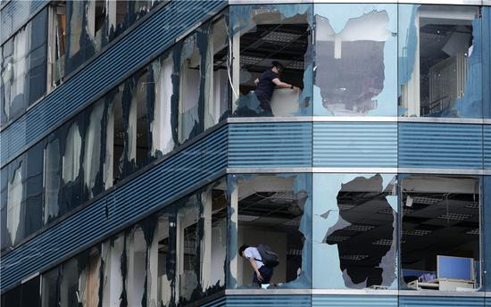 Workers start recovery work at a high-rise where super Typhoon Mangkhut blew out windows on Sunday in the Hong Kong Special Administrative Region. Mainland areas also were hard hit, with at least four deaths reported. (WANG SHEN/XINHUA)