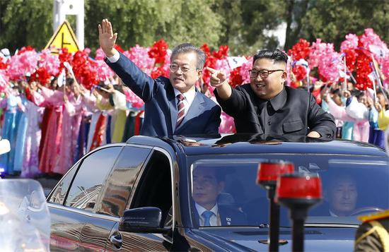 During a motorcade procession, Republic of Korea President Moon Jae-in and Democratic People's Republic of Korea top leader Kim Jong-un greet a welcoming crowd in Pyongyang on Tuesday. (Photo/Xinhua)