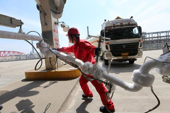An employee shifts the LNG pipeline after filling the transport vehicle at the CNPC LNG center in Jiangsu Province. (Photo by Xu Congjun/for China Daily)