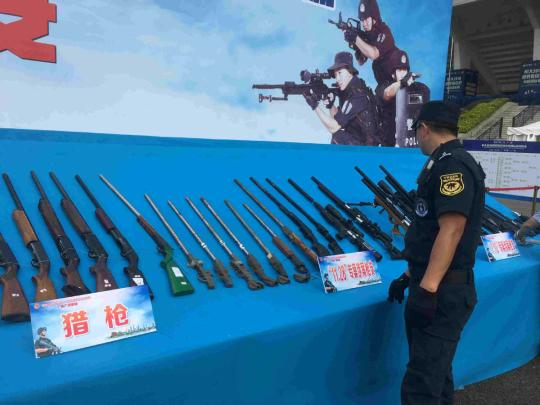 A policeman looks at guns seized in recent years at a ceremony in Guangzhou, South China's Guangdong province, on Sept 20, 2018. (Photo by Zheng Caixiong / chinadaily.com.cn)