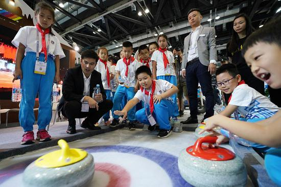 Primary-school students try their hand at curling during the World Winter Sports (Beijing) Expo on Wednesday at China National Convention Center. (Photo/Xinhua)