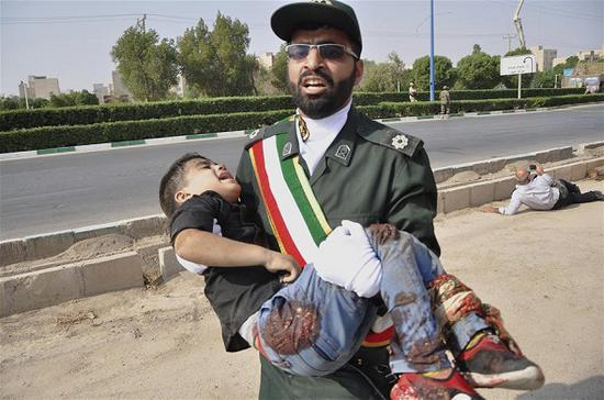 An Iranian soldier carries an injured boy during a terror attack in a military parade in Ahvaz, Iran, Sept. 22, 2018. At least 24 people were killed in a terror attack in a military parade in southwestern Iranian Ahvaz city on Saturday, official IRNA news agency reported. (Photo/Xinhua)