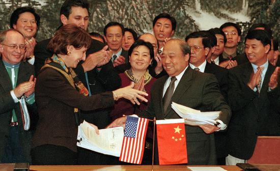 US Trade Representative Charlene Barshefsky (left) exchanges documents with Chinese Trade Minister Shi Guangsheng after signing a landmark agreement in Beijing in November 1999. The deal paved the way for China's entry into the WTO. (Photo by Xu Jingxing/China Daily)