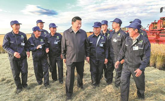 President Xi Jinping talks with workers at a State-owned farm in Jiansanjiang, Heilongjiang province, on Tuesday, the first day of his inspection visit to the province. He had detailed talks with farmworkers and managers on production and management. (Photo/Xinhua)