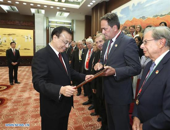 Chinese Premier Li Keqiang meets with a group of foreign experts and their relatives, who had recently received the Friendship Award, given annually by the Chinese government to honor outstanding foreign experts in China, in Beijing, capital of China, Sept. 30, 2018. Chinese Vice Premier Han Zheng also attended the meeting. (Xinhua/Pang Xinglei)
