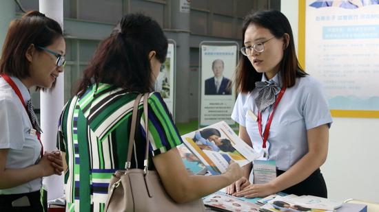 Representatives from an overseas IVF clinic introduce their service to a Chinese woman during an expo held in Chengdu, southwest China. / CGTN Photo