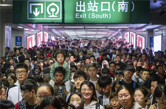 Large numbers of travelers move slowly through Nanjing Railway Station in Jiangsu province on Sunday. Many locations across the country saw traffic peaks on Oct 7, the last day of the weeklong National Day holiday. (SU YANG/FOR CHINA DAILY)