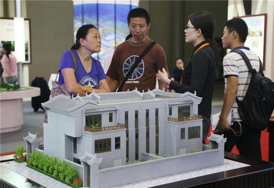A saleswoman introduces a housing project at a property fair in Beijing on Sept .13.( WU CHANGQING/FOR CHINA DAILY)