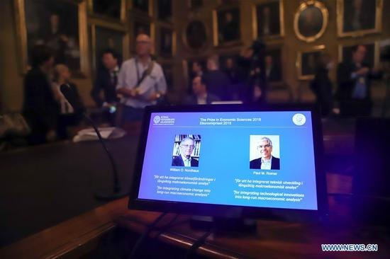 Photo taken on Oct. 8, 2018 shows a screen displaying the portraits of awarded economists William Nordhaus (L) and Paul Romer of the United States, in Stockholm, Sweden.  (Xinhua)
