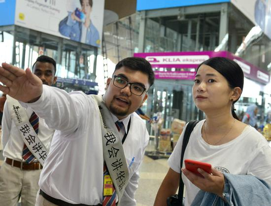 A Chinese-speaking assistant at Kuala Lumpur International Airport offers help to a Chinese tourist during the weeklong National Day holiday. The airport has increased the number of Mandarin-speaking staff to better serve Chinese tourists. (Photo/XINHUA)