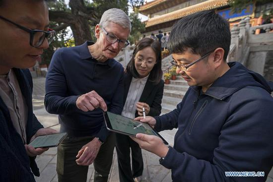 Liu Zhipeng (1st R), one of the founders of Xichuangzhu APP, shows Apple's CEO Tim Cook (2nd L) how to write calligraphy on iPad with Apple Pencil at Beijing Confucian Temple in Beijing, capital of China, on Oct. 10, 2018. Cook paid a visit to Beijing Confucian Temple and the Imperial College on Wednesday. (Xinhua/Cai Yang)