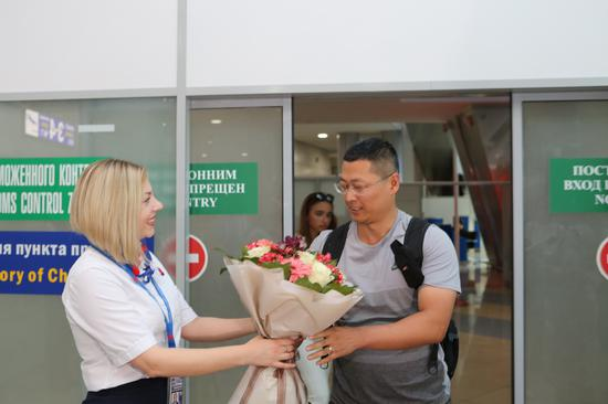 The first Chinese traveler to arrive at Minsk National Airport in Belarus under the new visa-free agreement receives flowers from an airport employee. China and Belarus implemented visa-free policies for their respective citizens on Aug. 10. (Photo/Xinhua)