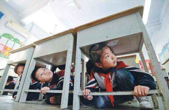 Primary school students crouch under desks during an earthquake drill on Friday in Handan, Hebei province. (Photo by Hao Qunying/For China Daily)