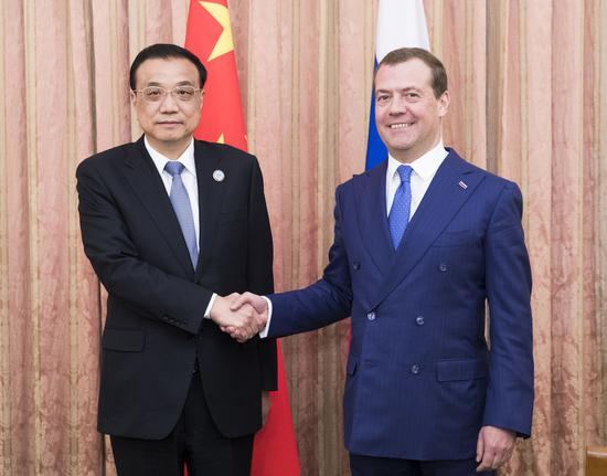 Chinese Premier Li Keqiang meets with his Russian counterpart Dmitry Medvedev on the sidelines of the 17th meeting of the Council of Heads of Government of the Shanghai Cooperation Organization in Dushanbe on Friday. (Photo/Xinhua)