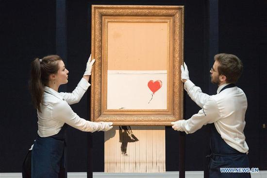 Sotheby's staff members present Banksy's
