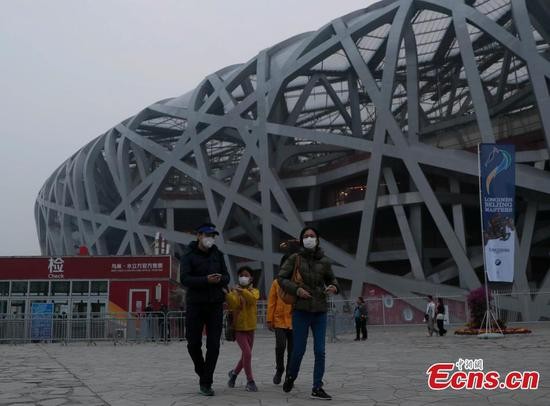 Tourists visit the area around National Stadium, also known as the Bird's Nest, on a smoggy day in Beijing, Oct. 14, 2018. (Photo: China News Service/Liu Guanguan)