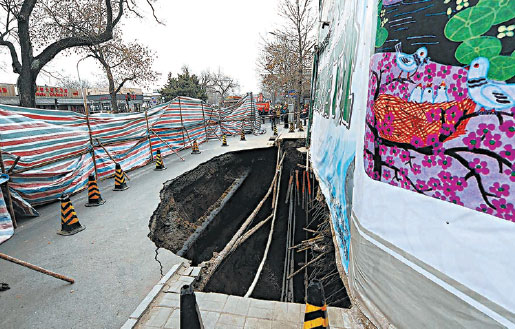 This photo taken on Jan 24, 2015 shows a big hole on a street in Beijing's Xicheng district. The hole has since been filled in with 1,400 cubic meters of concrete. (Photo by Xu Xiaofan / for China Daily)