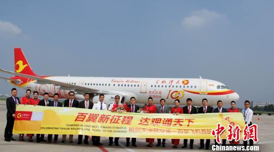Staff members of Tianjin Airlines pose before a plane. (File photo/China News Service)