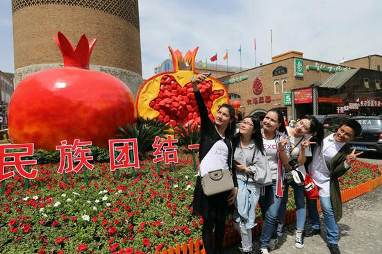 Visitors pose for a selfie at the entrance of the Xinjiang International Bazaar in Urumqi, capital of the Xinjiang Uygur autonomous region. (Photo by Li Xiongxin/For China Daily)