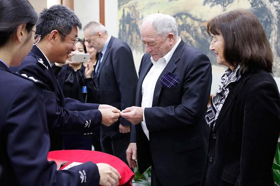 Kurt Wuthrich (second from right), winner of the Nobel Prize in Chemistry, and five other foreign nationals are granted permanent residence in China by the Shanghai Municipal Bureau of Public Security in April. (Photo by Yin Liqin/China News Service)