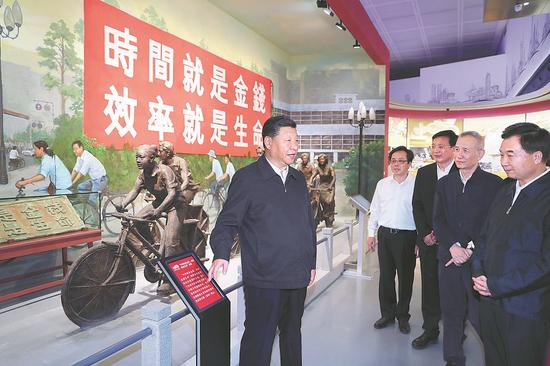 """President Xi Jinping, also general secretary of the Communist Party of China Central Committee, visits an exhibition in Shenzhen about the 40th anniversary of reform and opening-up in Guangdong province on Wednesday. The banner says, """"Time is money, efficiency is life"""". (Photo/Xinhua)"""